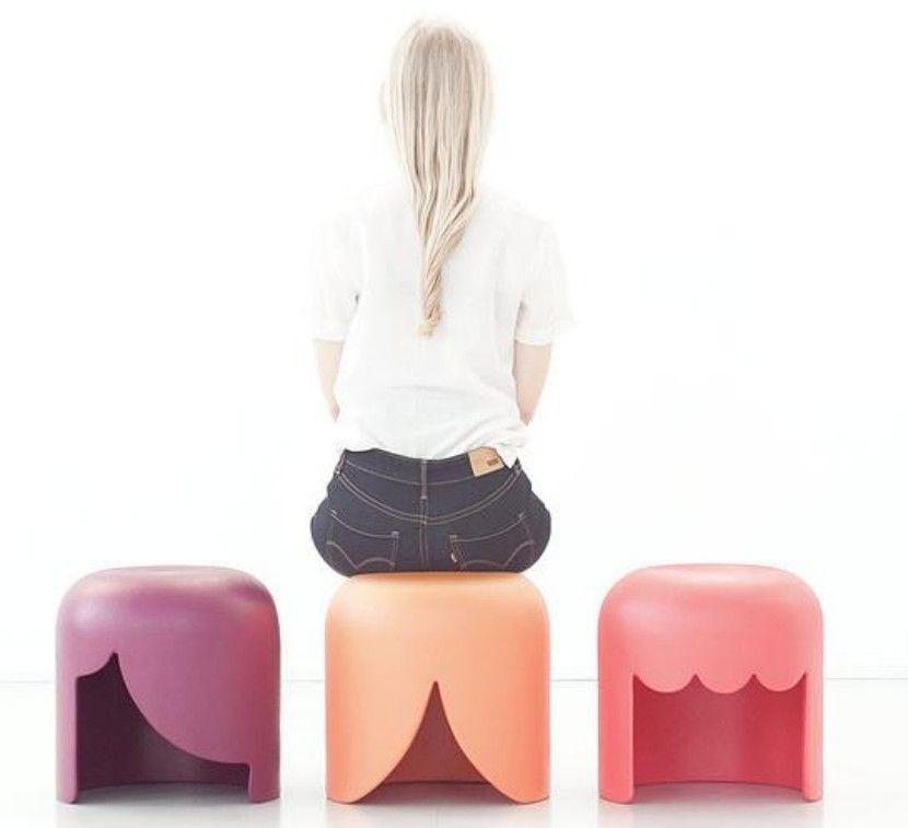 Chica sentada en unos de los tres taburetes
